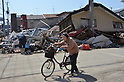 April 1st, 2011, Miyako, Japan - A woman pushes her bicycle passed a head of debris and destroyed townhouse in Miyako City, Iwate Prefecture, on April 1, 2011, three weeks after the city was devastated by a magnitude 9.0 earthquake and ensuing tsunami. (Natsuki Sakai/AFLO) [3615] -mis-...