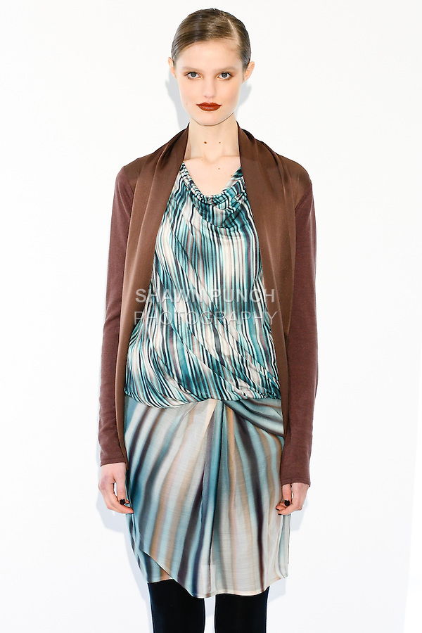 Model wears a knit cardigan top w/tie, illusion print twist top, and richter print skirt, by Fiona Cibani, for the Ports 1961 Pre-Fall 2011 L'heure bleue collection, December 8, 2010.