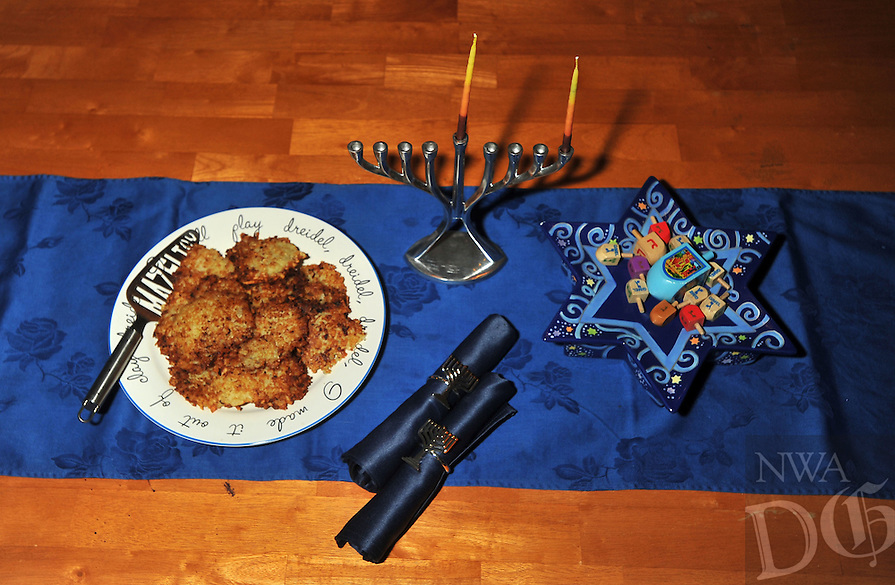 Photo Illustration  NWA Democrat-Gazette/MICHAEL WOODS • During Hanukkah, Jews eat foods fried in oil, like latkes (on plate) and sufganiot (a type of jelly doughnut), to commemorate the miracle of oil. When the Jews rededicated the Holy Temple, there was only enough oil to light the menorah for one day, but it would take eight days to get more oil. Miraculously, the oil lasted for eight days.