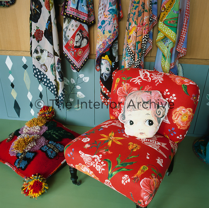 Brightly patterned scarves hang on a panelled and painted wall. In front stands a chair upholstered in vibrant red fabric with a floral pattern