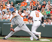 Casey Kotchman #13 of the Seattle Mariners fails to stop Adam Jones #10 of the Baltimore Orioles getting on first base during a MLB game at Camden Yards, on August 8 2010, in Baltimore, Maryland. Orioles won 5-4 in extra innings.
