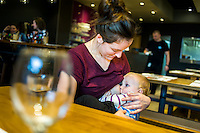 A mother breastfeeding her 10 month old son in a restaurant. The waiter is bringing the bill.<br /> <br /> Herefordshire, England, UK<br /> 09/01/2015<br /> <br /> &copy; Paul Carter / wdiip.co.uk