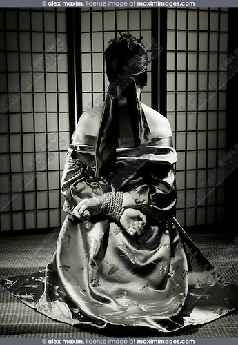 Asian woman in kimono with blindfolded eyes and her hands tied with bondage rope behind her back sitting on a straw mat