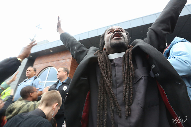 Rev. Osagyefo Sekou - Freeman Fellow with the Fellowship of Reconciliation - calls over 300 clergy and faith leaders to kneel, praying on the steps and parking lot of the Ferguson Police Station as part of the Ferguson October Clergy March.