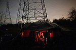 Campers stay warm in a tent heated by a propane burner at the SafeGround homeless tent camp in Sacramento, Calif., January 13, 2011.