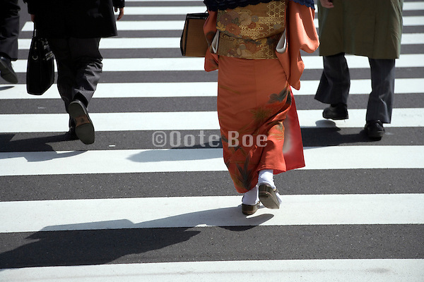 businessmen and woman in traditional Japanese dress walking
