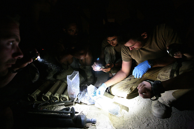 Canadian soldiers with the Royal 22nd Regiment examine papers and other materials found on three Taliban fighters they shot dead earlier that day in the village of Zalakhan in Kandahar province, Afghanistan. Also pictured is a U.S.-made 60mm mortar tube and four rounds of ammunition that the insurgents were carrying. The fighters were likely on their way to shoot the mortar rounds at a nearby Canadian base when they were killed. Aug. 8, 2009. DREW BROWN/STARS AND STRIPES