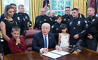 United States President Donald J. Trump, surrounded by men and women in uniform, about violence against police and signs a proclamation supporting police officers at The White House in Washington, DC, May 15, 2017. <br /> Credit: Chris Kleponis / Pool via CNP /MediaPunch
