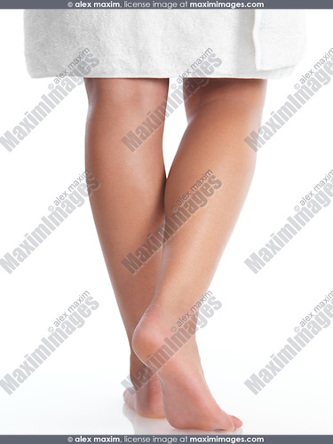 Closeup of legs of a young woman wrapped in a towel. Isolated on white background.