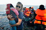A volunteer carries a child to safety as a rubber raft lands on a beach near Molyvos, on the Greek island of Lesbos, on October 30, 2015. The boat, which came from Turkey, was filled with refugees who paid Turkish traffickers huge sums for the trip. They were received in Greece by local and international volunteers, then proceeded on their way toward western Europe.