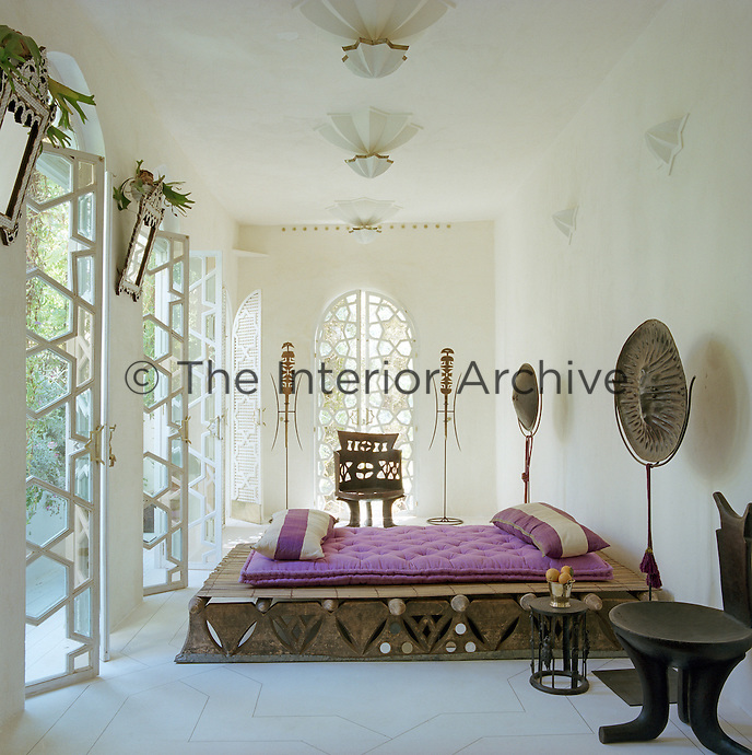 The bespoke wooden bed frame complements the tribal artefacts on display in this guest bedroom