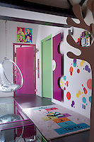 "A radiator in the form of a large slice of pink cheese, a coat rack in the shape of a tree and a wall covered in large ""paint splatter"" stickers all contribute to ensure a bright and cheerful nursery"