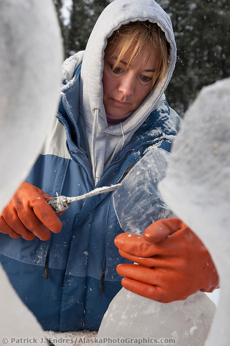 """Alaska sculptor Kristi Stewart, carves away on a single block, abstract sculpture titled """"It is what it is"""" during the 2009 World Ice Art Championships in Fairbanks, Alaska."""