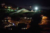 Nogales, Arizona.USA.October 24, 2006..The moon rises on the border fence (center of the frame)between Nogales USA (in the foreground), and Nogales Mexico (in the background).