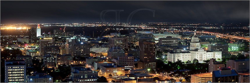 Taken from a bird's eye view above Austin, this image looks down on the Texas State Capitol and the UT Tower at night.