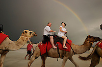 Tourists ride a camel on the beach under a rainbow with the Camel Caravan at Cable Beach.<br /> Broome is one of the few tourist centers that actually has visitors during the wet.  The camel rides are prominently displayed on the travel brochures.<br /> The city has 15,000 regular residents, but swells to 100,000 in tourist season.<br /> April 2000 Eye of cyclone went 40km south of Broome. 80 mile beach is 50km south of Broome and gets horrendous weather and cyclones are always slam into this spot.