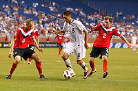 7 June 2011: USA Men's National Team forward Clint Dempsey (8) dribbles the ball between Canada defender Kevin McKenna (4) and midfielder Nikolas Ledgerwood (2) as Canada midfielder Nikolas Ledgerwood (2) defends during the CONCACAF soccer match between USA MNT and Canada MNT at Ford Field Detroit, Michigan. USA won 2-0.