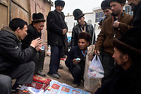Uighur men purchase traditional Chinese medicine from a street seller at the Sunday Market at the Grand Bazaar in Kashgar, Xinjiang, China. Throughout history, the Kashgar Sunday Market has been an important stop on the Silk Road.