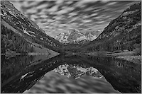 Clouds float over the Maroon Bells and Maroon Lake in the Maroon Bells Wilderness area. This Colorado image used an exposure of over 2 minutes to allow movement in the clouds. The stillness of the early morning produced a mirror-like reflection in the calm, clear waters.