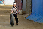 Five-year old Ali Mustafa Rahil plays with a tire in the Aamer al Sanad refugee settlement in Kab Elias, a town in Lebanon's Bekaa Valley which has filled with Syrian refugees. Lebanon hosts some 1.5 million refugees from Syria, yet allows no large camps to be established. So refugees have moved into poor neighborhoods or established small informal settlements, such as Aamer al Sanad, in border areas. International Orthodox Christian Charities, a member of the ACT Alliance, provides support for refugees in Kab Elias, including a community clinic.