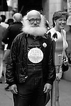 """Elderly man standing along sidewalk looking at camera smiling wearing on his chest a sign that says """"Jesus Christ is Right On"""" with passerby smiling at him, street scene along University Avenue,  """"The Ave""""  Seattle, Washington State USA"""