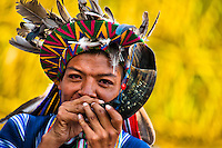 """A native from the Kamentsá tribe, wearing a colorful headgear, plays horn trumpet during the Carnival of Forgiveness, a traditional indigenous celebration in Sibundoy, Colombia, 12 February 2013. Clestrinye (""""Carnaval del Perdón"""") is a ritual ceremony kept for centuries in the Valley of Sibundoy in Putumayo (the Amazonian department of Colombia), a home to two closely allied indigenous groups, the Inga and Kamentsá. Although the festival has indigenous origins, the Catholic religion elements have been introduced and merged with the shamanistic tradition. Celebrating annually the collaboration, peace and unity between tribes, they believe that anyone who offended anyone may ask for forgiveness this day and all of them should grant pardons."""