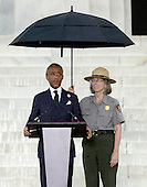 Reverend Al Sharpton, founder and president of the National Action Network, makes remarks as a U.S. Park Police officer holds an umbrella to shield her from the rain at the Let Freedom Ring ceremony on the steps of the Lincoln Memorial to commemorate the 50th Anniversary of the March on Washington for Jobs and Freedom.<br /> Credit: Ron Sachs / CNP