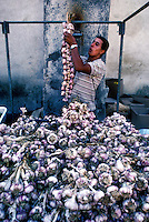 Provence, France- Man hanging garlic for sale in the market of Ramatuelle.  Photograph by Owen Franken