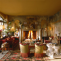 A pair of Ottoman sofas and matching armchairs infront of a blazing fire in the drawing room of this Turkish house