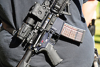 """Phoenix, Arizona. January 19, 2013 - A protester displays an automated gun during Saturday's rally in Phoenix to oppose potential new laws that would limit access to guns and ammunition in the United States. As President Barack Obama proposed new gun regulations last week, gun owners demonstrated against it with national """"Guns Across America"""" rallies to defend the Second Amendment. Dozens showed up at the Arizona State Capitol, many of them carrying weapons. Photo by Eduardo Barraza © 2013"""