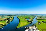Nederland, Noord-Brabant, Gemeente Waspik, 23-08-2016; Overdiepsche polder: in het kader van het programma 'Ruimte voor de Rivier' (bescherming tegen hoogwater door rivierverruiming), is de dijk langs de Bergsche Maas (links in beeld) verlaagd. Bij hoogwater kan de Overdiepse polder overstromen. De boerderijen in de polder zijn gesloopt en verplaatst naar de dijk van het Oude Maasje. De nieuwe boerderijen met bijgebouwen staan op terpen.<br /> Depoldering of Overdiep Polder, farms are relocated and built on mounds. This makes it possible for the river to overflow the polder in case of heigh waters.<br /> luchtfoto (toeslag op standard tarieven);<br /> aerial photo (additional fee required);<br /> copyright foto/photo Siebe Swart