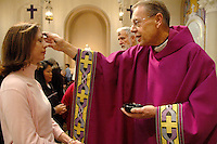 Monsignor Lloyd Torgerson places ashes onto the forehead of parishiner Belinda Gonzales at St. Monica during the Ash Wednesday service on Feb. 21 2007.