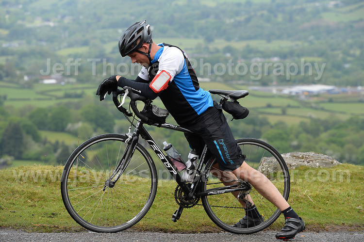 Competitors climb the challenging iconic and notorious 6km 10% stretch of road namely The Tumble during the Wales Velothon 2016 140km route cycling race. Stretching the calves.  <br /> <br /> <br /> Jeff Thomas Photography -  www.jaypics.photoshelter.com - <br /> e-mail swansea1001@hotmail.co.uk -<br /> Mob: 07837 386244 -