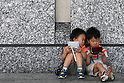 May 9, 2010 - Tokyo, Japan - Two Japanese boys play Nintendo's portable video game 'DS' in front of the official Pokemon store in Tokyo on May 9, 2010. Nintendo recently announced that the DS handheld device had become the best selling gaming handheld of all time, with a total of 129 million units sold. The DS 'family' have surpassed the &quot;Game Boy&quot; series which hit 118 million over two decades.