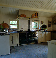 This country-style kitchen has an Aga or range and a flag-stone floor