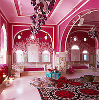 The sequinned mattresses in this pink living area are topped with cushions covered in Art Deco-era saris and the ceiling lights are mercury-glass drops