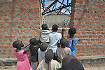 Children anxiously observe construction of their new school in the Southern Sudanese village of Mankaro. The school is being constructed by the United Methodist Committee on Relief (UMCOR). Families here are rebuilding their lives after returning from refuge in Uganda in 2006 following the 2005 Comprehensive Peace Agreement between the north and south. .