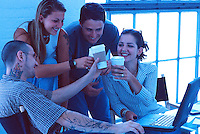 Smiling young adults at work together toast their success with coffee in a casual office setting.