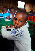 Seven-year-old Maimlina Chepkemoi in class   <br /> Rhonda slum Nakuru, Kenya, Africa 2002.<br /> Maimlina&rsquo;s twenty-two-year-old mother has disappeared, leaving her and her sister with their grandmother, who works as a vegetable seller. They have never known their father. When I first visited the Rhonda slum at Lake Nakuru, I was struck not only by the beauty of the children who lived there but by their optimism and determination in overcoming the adverse conditions surrounding them. Most of these children have been affected in some way by the AIDS epidemic. Many are orphaned or living with grandparents in shanty houses that cost about $5 a month to rent.<br /> Aid organization, Learning and Development Kenya (LDK), initiated the Rhonda Children&rsquo;s Home and Learning Center in the Rhonda slums. Like an oasis, this school helps to educate children of all abilities to help them eventually merge into some sort of educational system. The organization also offers the community support the children or their families may need.