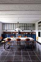 The kitchen is furnished with a rustic refectory table surrounded by a set of school chairs by Willy van der Meeren with an antique ceramic stove beside a black stone sink along the far wall