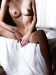 Artistic nude closeup of a body of a naked woman sitting on a bed