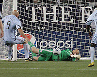 Preston Burpo saves a goal in the first half as Colorado Rapids forward Conor Casey (9) approaches.  The Colorado Rapids defeated the New England Revolution, 2-1, at Gillette Stadium on April 24.2010