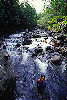 Mother and daughter playing in clear stream/ waterfall, Tahiti, French Polynesia