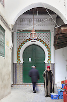 One of the entrances to the Jamaa el Kebir or Great Mosque, with a green door under a horseshoe arch surrounded by traditional zellige tilework, 19th century, in the medina or old town of Tetouan, on the slopes of Jbel Dersa in the Rif Mountains of Northern Morocco. Tetouan was of particular importance in the Islamic period from the 8th century, when it served as the main point of contact between Morocco and Andalusia. After the Reconquest, the town was rebuilt by Andalusian refugees who had been expelled by the Spanish. The medina of Tetouan dates to the 16th century and was declared a UNESCO World Heritage Site in 1997. Picture by Manuel Cohen