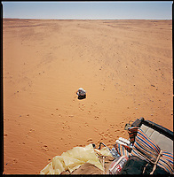 Sahara desert, Libya-Chad, November/December 2004..Every week, a convoy of 40 privately owned Libyan trucks loaded by the WFP with about 1000 metric tons of western food aid cross 2500 km of deep desert across Libya and Chad to reach more than 200 000 refugees from Darfur in camps near the Sudanese border. Moussa stops his truck for the noon prayer in the desert blazing sun.