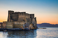 Sunrise at Naples Harbor, Castel dell'Ovo, Naples Italy. The Castel dell'Ovo is the oldest standing fortification in Naples. The island of Megaride was where Greek colonists from Cumae founded the original nucleus of the city in the 6th century BC. Its location affords it an excellent view of the Naples waterfront and the surrounding area. In the 1st century BC the Roman patrician Lucius Licinius Lucullus built the magnificent villa Castellum Lucullanum on the site. Fortified by Valentinian III in the mid-5th century, it was the site to which the last western Roman emperor, Romulus Augustulus, was exiled in 476.