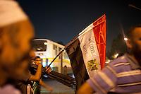 EGITTO, IL CAIRO 9/10 settembre 2011: assalto all'ambasciata israeliana. Migliaia di manifestanti egiziani, ancora infuriati per l'uccisione di cinque guardie di frontiera egiziane da parte dell'esercito israeliano, hanno fatto irruzione nella sede diplomatica israeliana e sono stati poi sgomberati da esercito e polizia egiziana. Nell'immagine: manifestanti con bandiere dell'Egitto su cui &egrave; scritto &quot;Noi amiamo l'Egitto&quot;. Sullo sfondo un autobus.<br /> Egypt attack to the Israeli embassy  Attaque &agrave; l'ambassade israelienne Caire