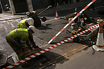 Construction crew grind at the road surface surrounded by diagonals of red and white stripes of their works site.