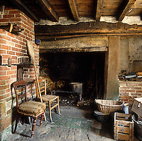 The abandoned kitchen with its soot-blackened fireplace and brick bread oven