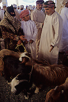 Sinao, Oman.  A woman owner of a goat bargains with a potential buyer in the days immediately before the Eid al-Adha.  Omanis, like all Muslims who can afford to do so, will sacrifice a goat to celebrate the Eid al-Adha (Feast of the Sacrifice), the annual feast through which Muslims commemorate God's mercy in allowing Abraham to sacrifice a ram instead of his son, to prove his faith.